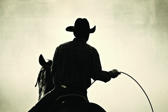 cowboy at the rodeo - shot backlit against big cloud of dust, co
